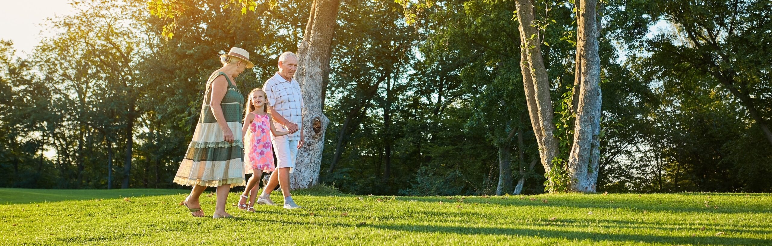 Seniors with granddaughter walking outdoors. People in summer.