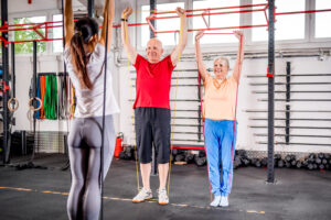Alpine Cardiology Senior people with trainer using resistance band doing exercises at the gym