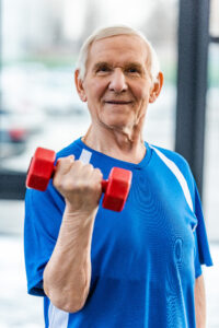 Alpine Cardiology smiling senior sportsman exercising with dumbbell at gym